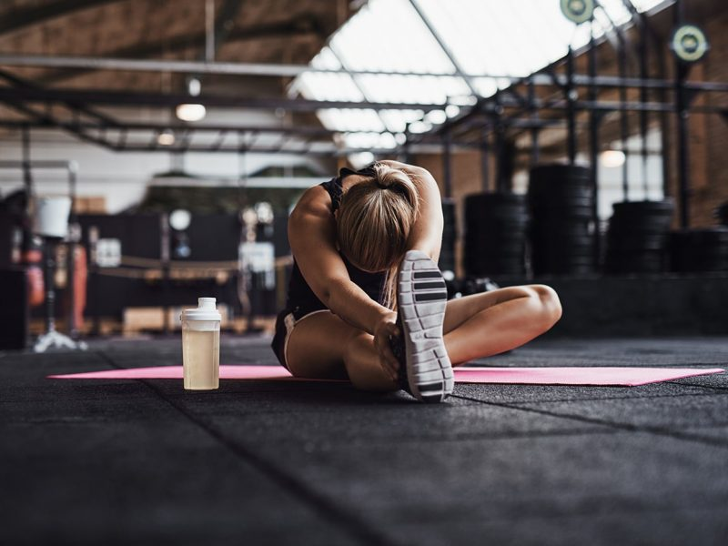 fit-young-woman-doing-stretches-on-a-gym-floor-QVWG8LX-min.jpg